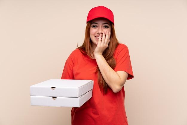 Ragazza dell'adolescente di consegna della pizza che tiene una pizza sopra la parete isolata con espressione facciale di sorpresa