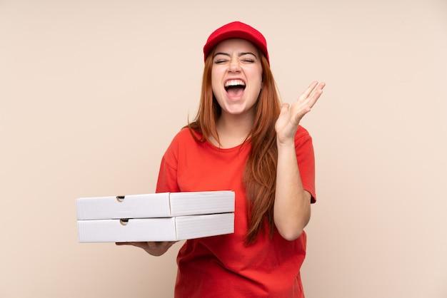 Ragazza dell'adolescente di consegna della pizza che tiene una pizza sopra la parete isolata infelice e frustrata con qualcosa
