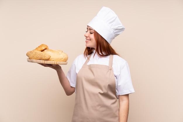 Ragazza dell'adolescente di redhead in uniforme del cuoco unico.