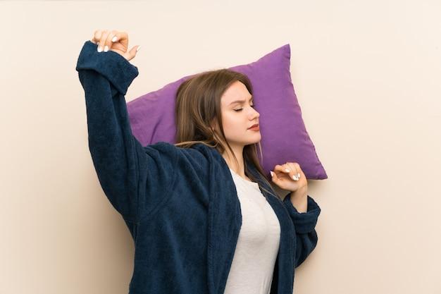 Ragazza dell'adolescente in pigiama sopra isolato e che sbadiglia
