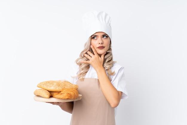 Ragazza dell'adolescente in uniforme del cuoco unico. panettiere femminile che tiene una tavola con parecchi pani sopra fondo bianco isolato che pensa un'idea