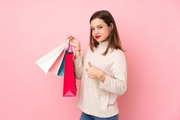 Ragazza dell'adolescente isolata sui sacchetti della spesa rosa della tenuta della parete e con il pollice su