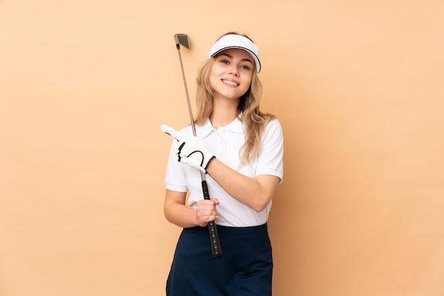 Ragazza dell'adolescente isolata sulla parete beige che gioca golf e che indica il laterale