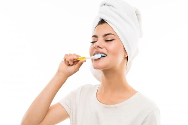 Ragazza dell'adolescente sopra bianco isolato che spazzola i suoi denti