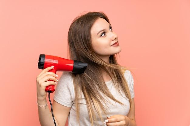Ragazza dell'adolescente sopra il rosa con il fon