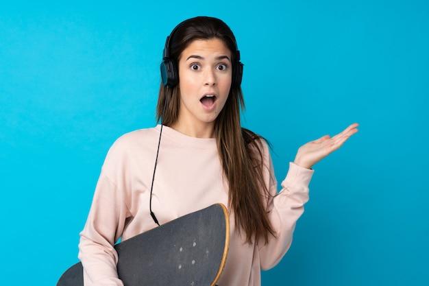 Ragazza dell'adolescente sopra la parete blu isolata con un pattino e fare il gesto di sorpresa