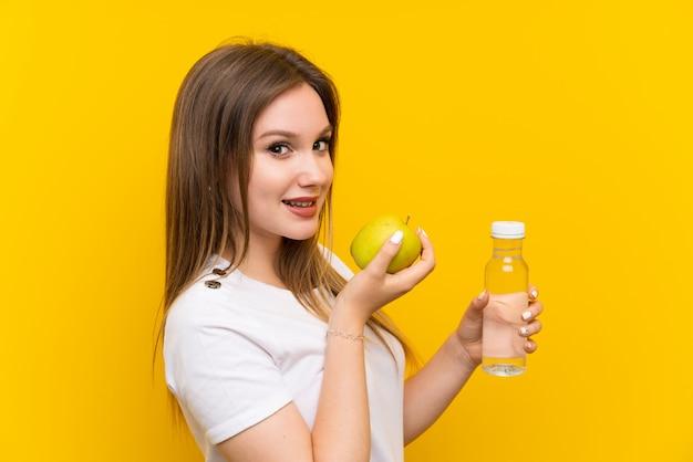 Ragazza dell'adolescente sopra la parete gialla con una mela e una bottiglia di acqua