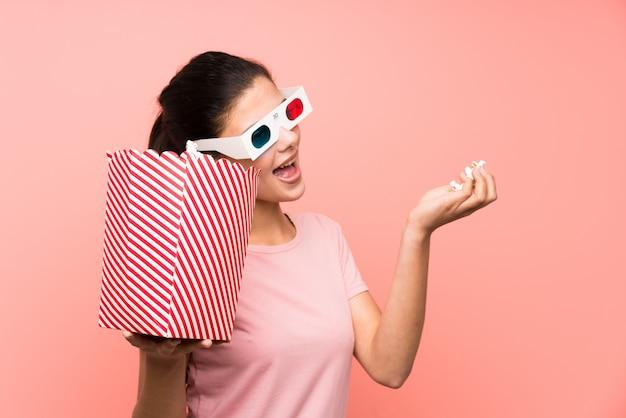 Ragazza dell'adolescente sopra la parete rosa isolata che mangia i popcorn con i vetri 3d
