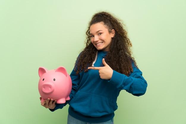 Ragazza dell'adolescente sopra la parete verde che tiene un porcellino salvadanaio