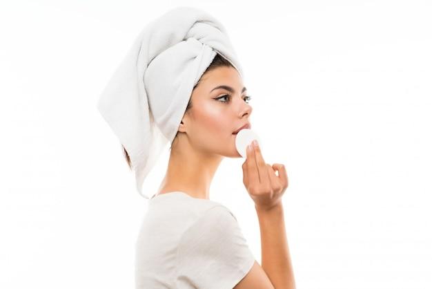Ragazza dell'adolescente sopra trucco wallremoving bianco isolato dal suo fronte con il cuscinetto di cotone