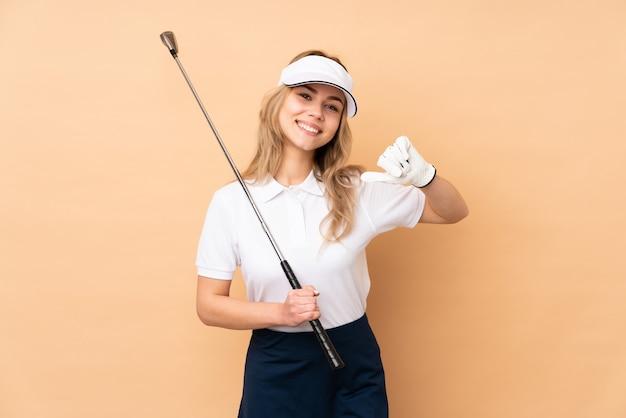 Ragazza dell'adolescente su beige che gioca golf e fiera di se stesso