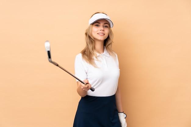 Ragazza dell'adolescente su beige che gioca golf