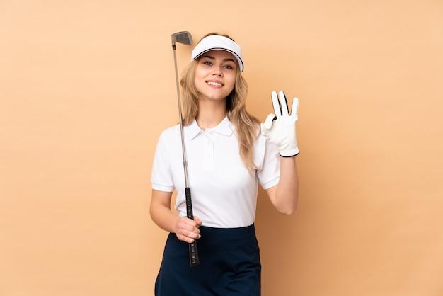 Ragazza dell'adolescente sulla parete beige che gioca golf che fa segno giusto