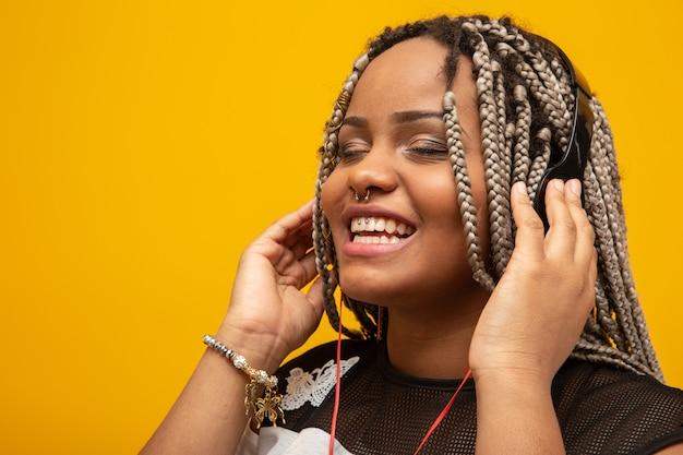 Ragazza dell'afroamericano che ascolta la musica sulle cuffie su giallo
