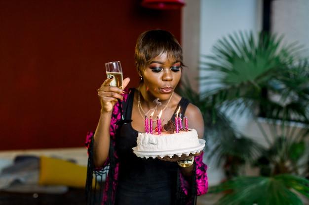 Ragazza dell'afroamericano che celebra il suo compleanno e soffiando le candeline sulla bella torta al cioccolato di compleanno