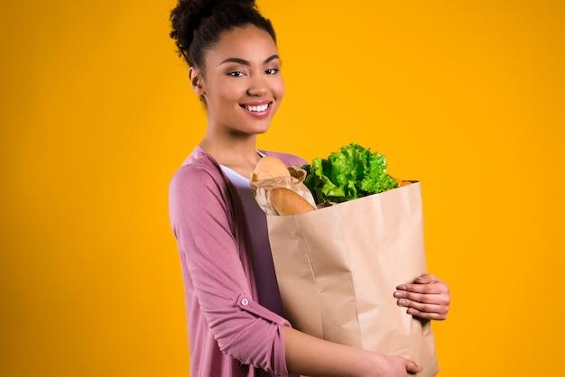 Ragazza dell'afroamericano con generi alimentari.