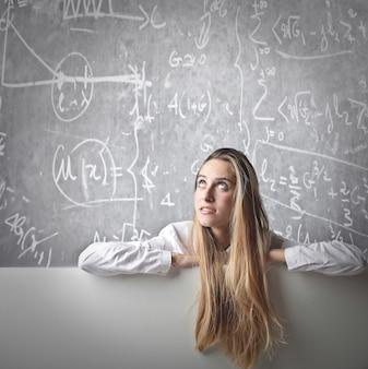 Ragazza dell'allievo che pensa alla matematica