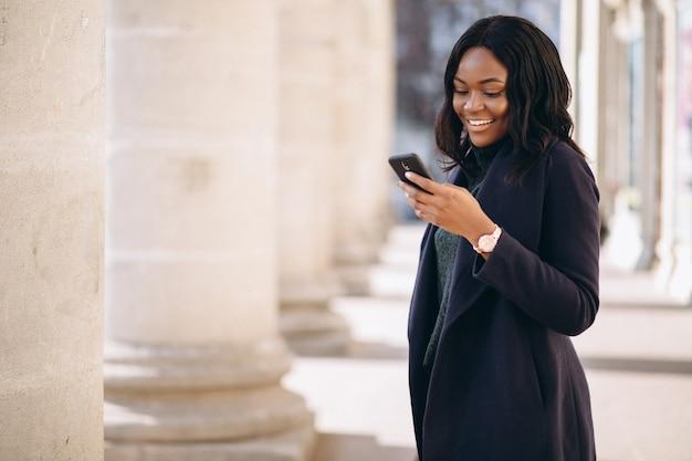 Ragazza dell'allievo dell'afroamericano con il telefono dall'università