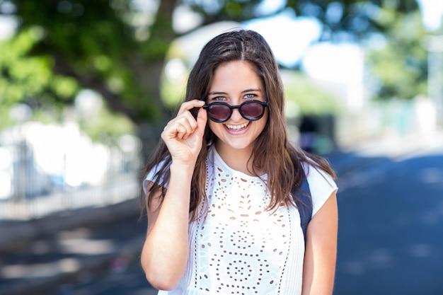 Ragazza dell'anca che tiene i suoi occhiali da sole per le strade