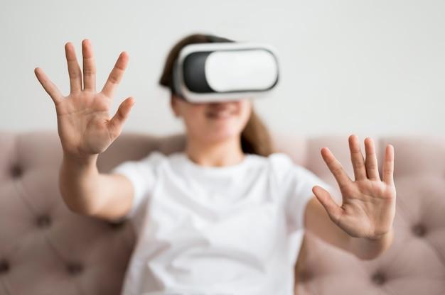 Ragazza dell'angolo alto con la cuffia avricolare di realtà virtuale