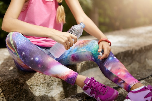Ragazza dell'atleta che si siede sul marciapiede e acqua potabile dalla bottiglia di plastica durante la pausa di allenamento cardio.