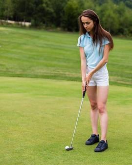 Ragazza della foto a figura intera che colpisce la palla da golf