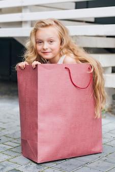 Ragazza della foto a figura intera che si siede in un sacchetto del regalo