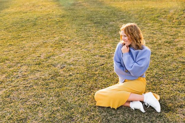Ragazza della foto a figura intera che si siede sull'erba