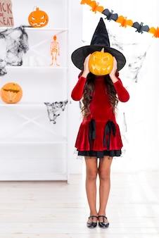 Ragazza della foto a figura intera che tiene la zucca di halloween