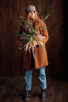 Ragazza della foto a figura intera con la posa dei fiori
