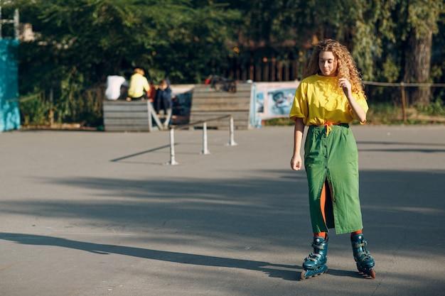 Ragazza della giovane donna in vestiti verdi e gialli e calze arancio con il pattinaggio a rotelle riccio dell'acconciatura nel parco dello skate