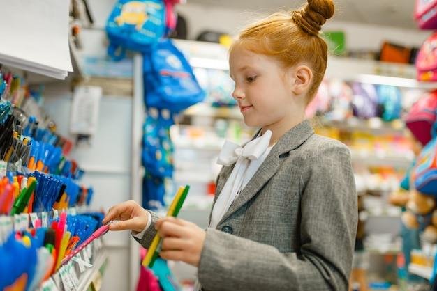 Ragazza della scuola che sceglie una penna in cartoleria