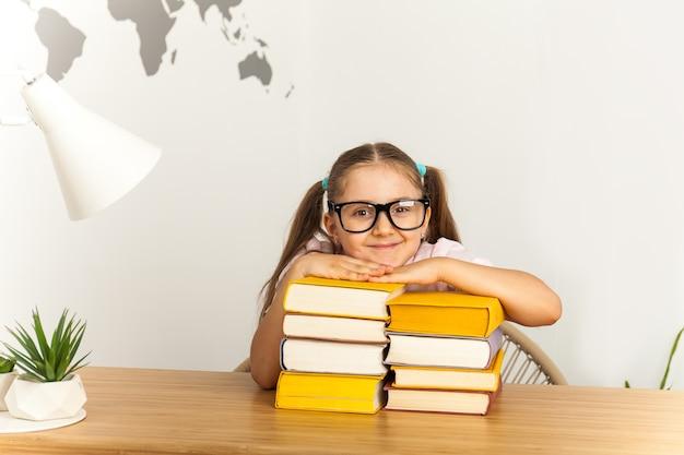 Ragazza della scuola con gli occhiali da sole con molti libri a scuola