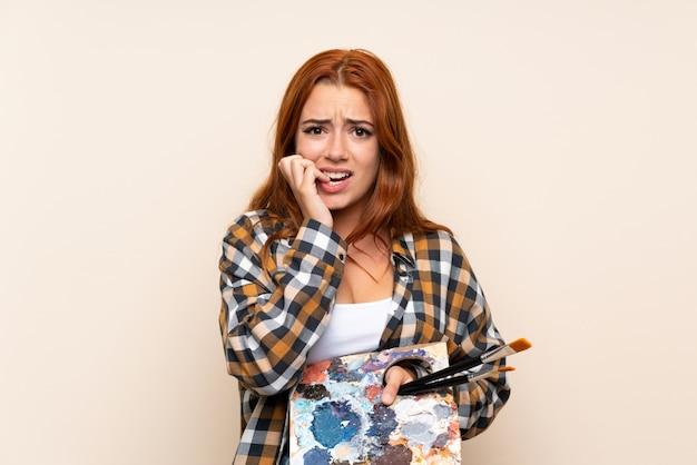 Ragazza della testarossa dell'adolescente che giudica una tavolozza nervosa e spaventata