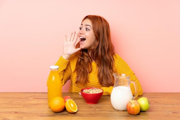 Ragazza della testarossa dell'adolescente che mangia prima colazione in una tavola che grida con la bocca spalancata