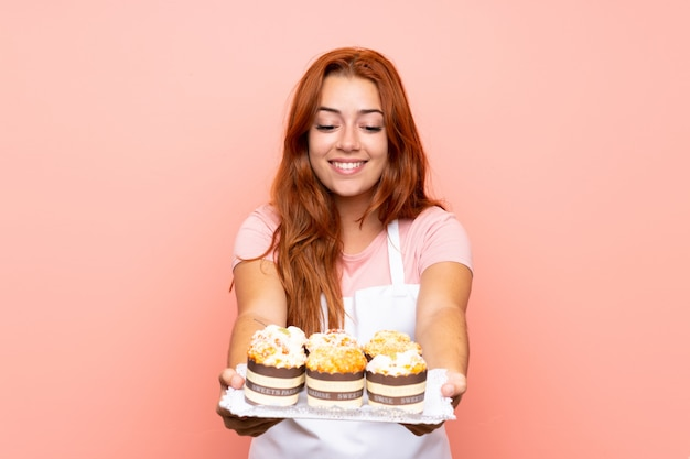 Ragazza della testarossa dell'adolescente che tiene i lotti di mini torte differenti sopra fondo rosa isolato