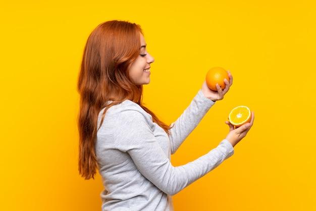 Ragazza della testarossa dell'adolescente che tiene un'arancia sopra giallo isolato