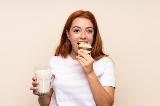 Ragazza della testarossa dell'adolescente che tiene un bicchiere di latte e un muffin sopra la parete isolata