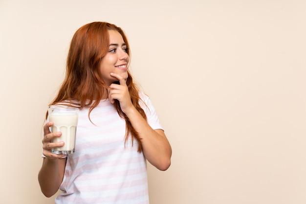 Ragazza della testarossa dell'adolescente che tiene un bicchiere di latte sopra fondo isolato che pensa un'idea e che guarda lato