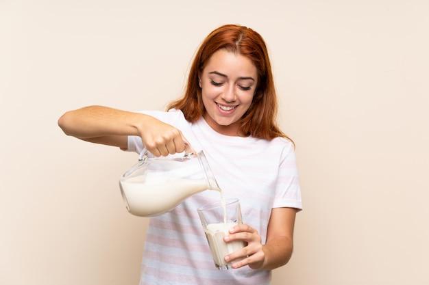 Ragazza della testarossa dell'adolescente che tiene un bicchiere di latte sopra fondo isolato