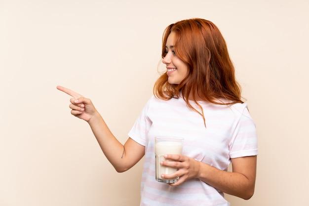 Ragazza della testarossa dell'adolescente che tiene un bicchiere di latte sopra la parete isolata che indica il lato per presentare un prodotto