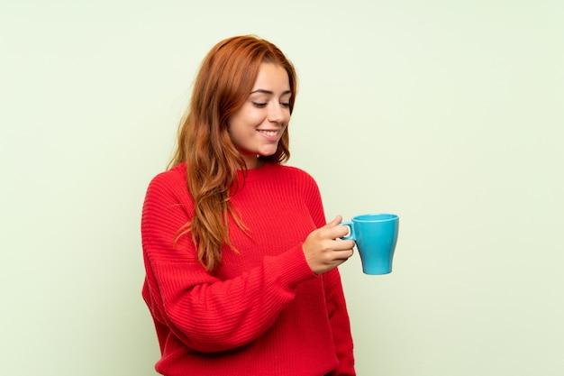 Ragazza della testarossa dell'adolescente con il maglione sopra fondo verde isolato che tiene tazza di caffè calda
