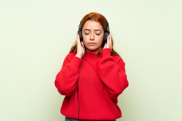 Ragazza della testarossa dell'adolescente con il maglione sopra la parete verde isolata che ascolta la musica con le cuffie