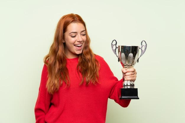 Ragazza della testarossa dell'adolescente con il maglione sopra la parete verde isolata che tiene un trofeo