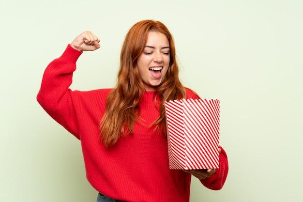 Ragazza della testarossa dell'adolescente con il maglione sopra la parete verde isolata che tiene una ciotola di popcorn