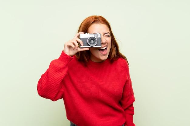 Ragazza della testarossa dell'adolescente con il maglione sopra la parete verde isolata che tiene una macchina fotografica