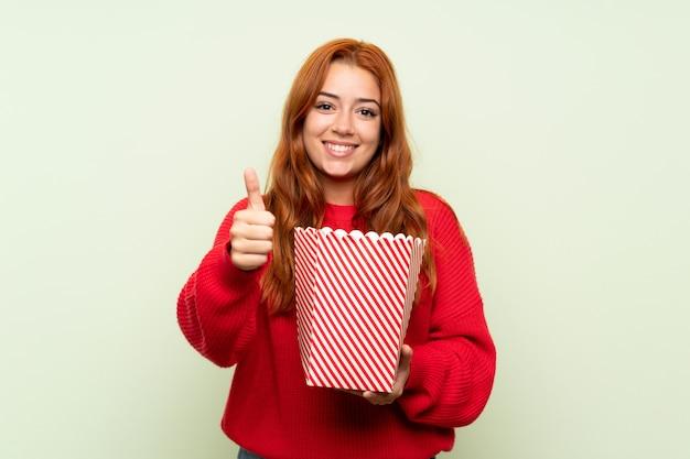 Ragazza della testarossa dell'adolescente con il maglione sopra verde isolato che tiene una ciotola di popcorn