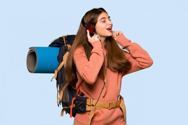 Ragazza della viandante che ascolta la musica con le cuffie sul blu