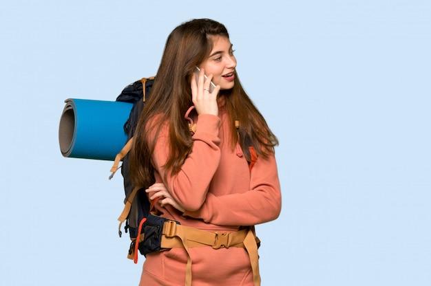 Ragazza della viandante che mantiene una conversazione con il telefono cellulare sul blu