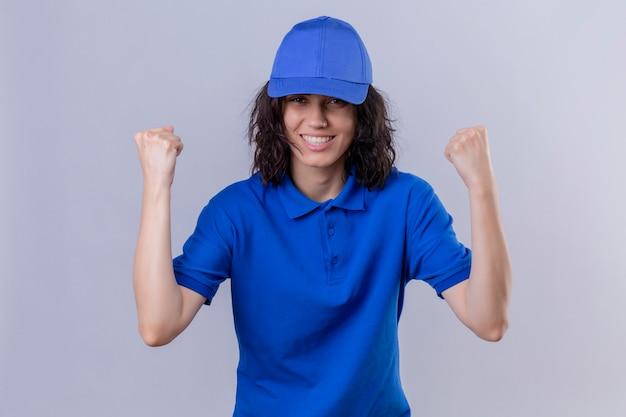 Ragazza delle consegne in uniforme blu e berretto che sembra uscito rallegrandosi del suo successo e della vittoria stringendo i pugni con gioia felice di raggiungere il suo scopo e gli obiettivi in piedi sul bianco isolato